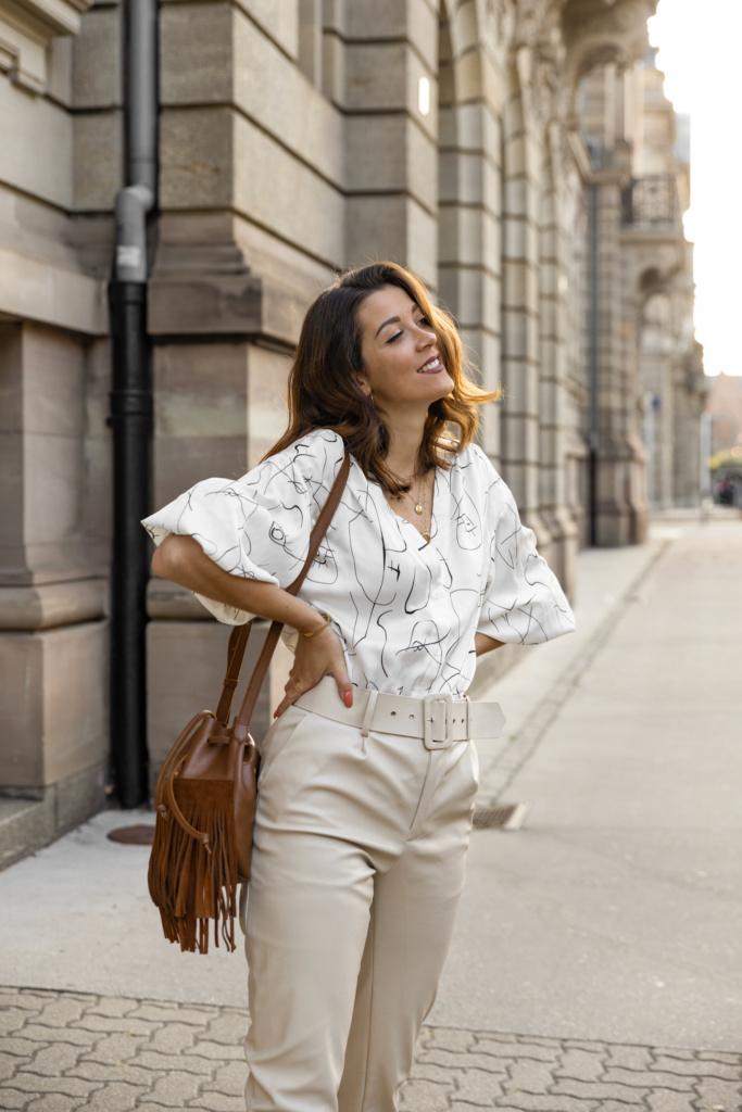 Look d'automne blouse à motif, pantalon cuir et sac à franges